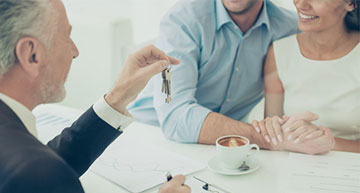 Happy couple sitting across from a real estate agent holding house keys | Representing Buyers